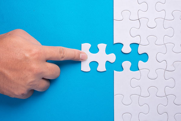 Hand holding piece of white puzzle on bl