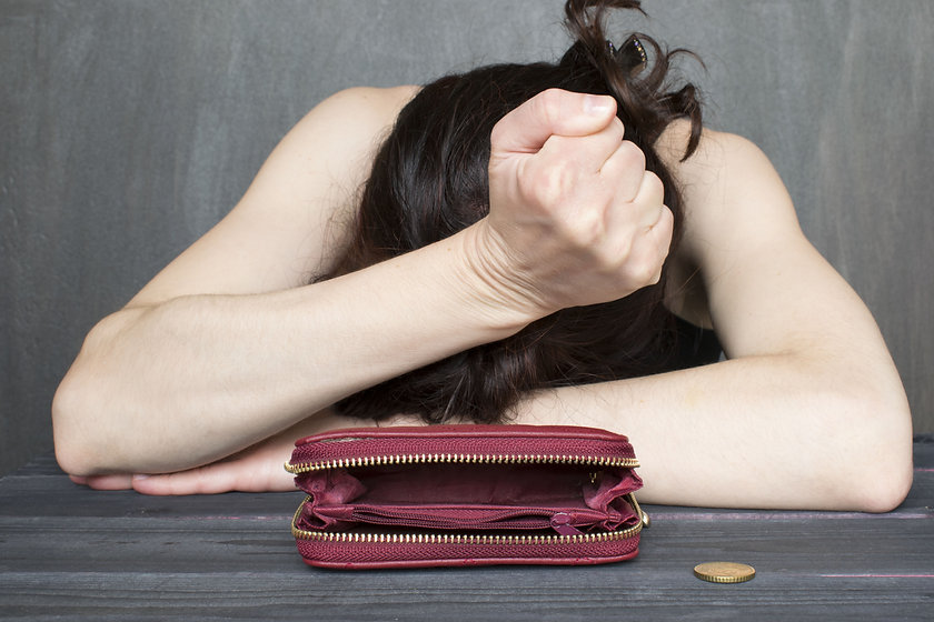 Financial difficulties concept, young frustrated woman sitting next to an old empty wallet