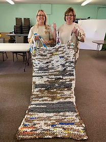 Volunteers holding up a finished plarn mat for the homeless