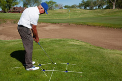 Setup for high lofted pitch using open stance and open clubface and target aiming rod