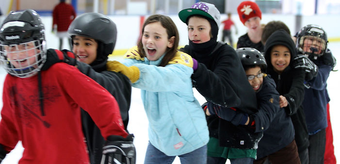 Kids ice skating in a conga line