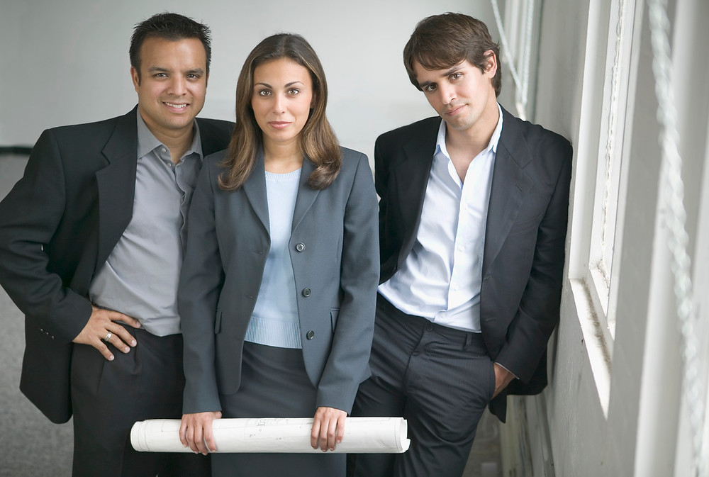Two young businessmen and a young businesswoman looking at camera