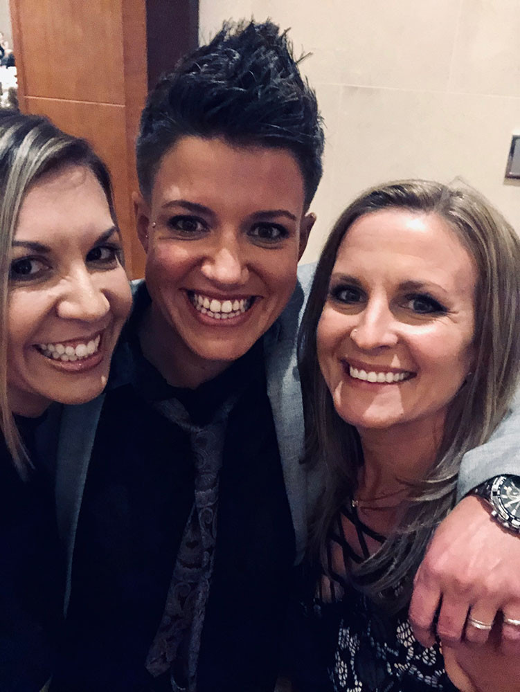 three women smiling close to each other