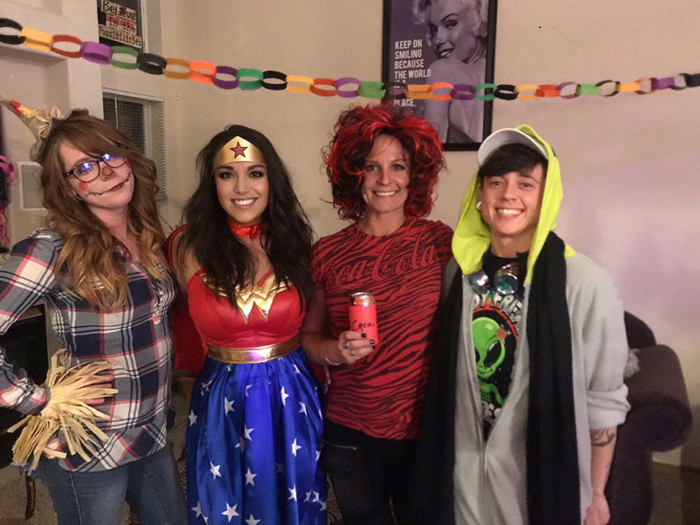 four smiling people in their Halloween costumes