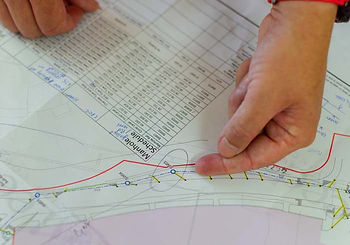 A civil engineer points at a location on a map