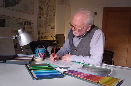 Architectural Illustrator Stephen Peart sits at his desk in his Norfolk home studio and illustrates. Foreground displays a range of coloured pencils.