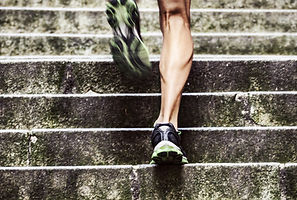 back of a person's legs running up stairs