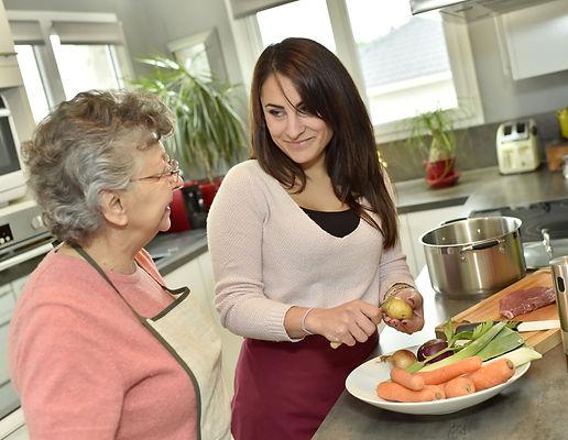 Homecare cooking dinner for elderly woman