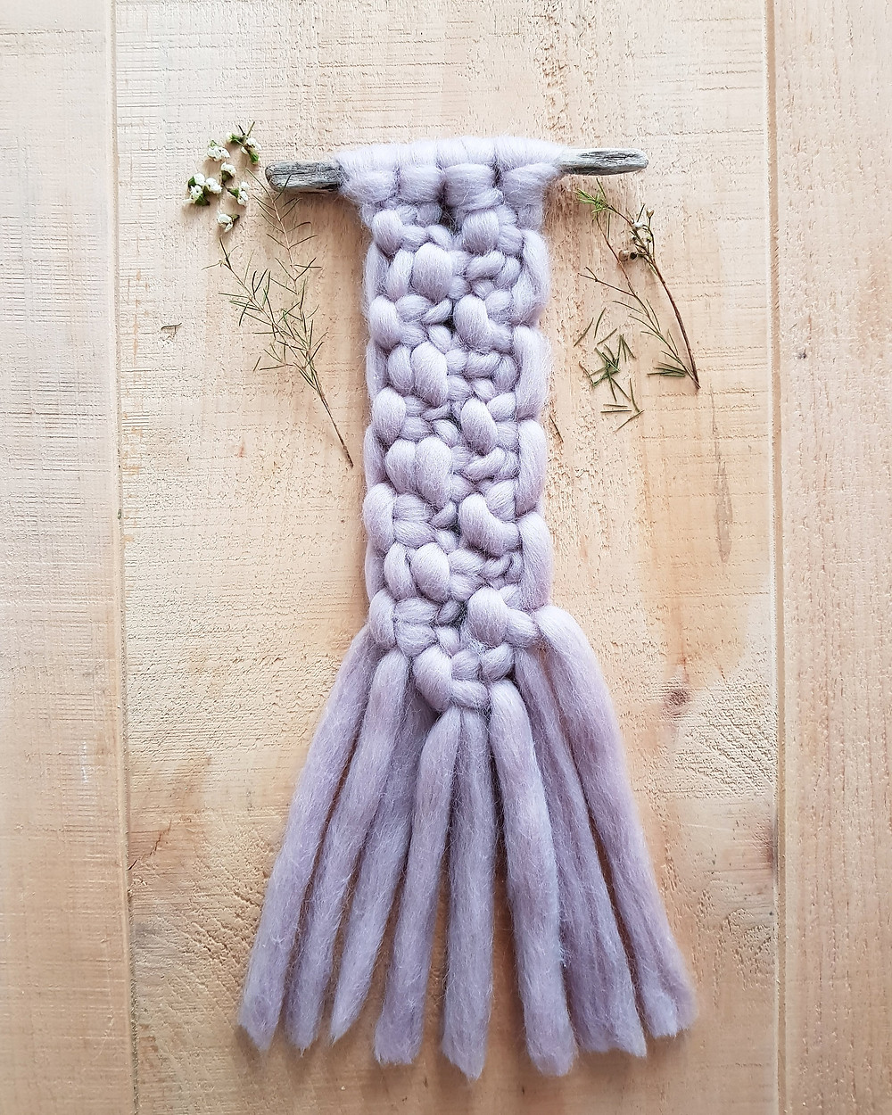 Purple macrame wall hanging made from wool on drift wood