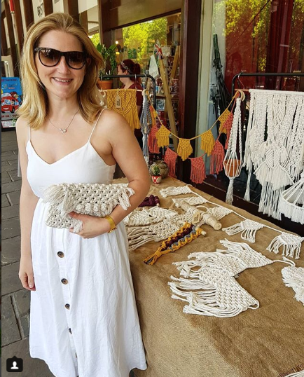Mame Artist in dress infront of craft stall with fiber art - Profile picture of Sarah Waddilove of Urban Rose Macrame