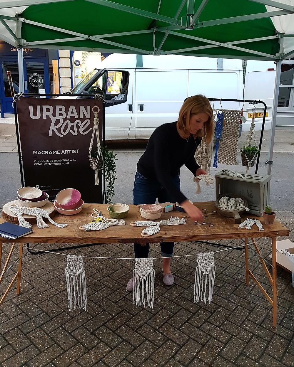 Macrame Artist attending to Craft stall with textiles art and Urban Rose backdrop