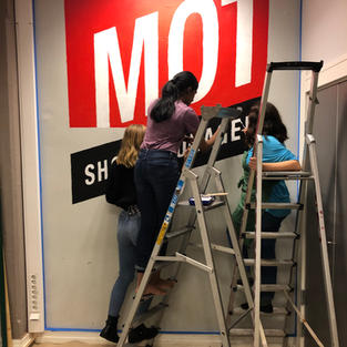 Students painting the MOT logo in the hallway