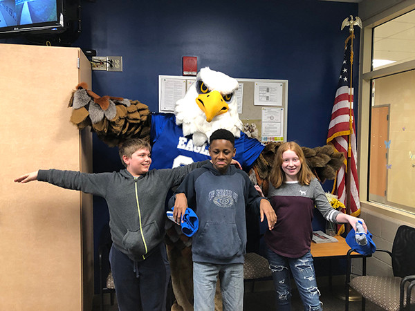 Students in the school office with mascot.