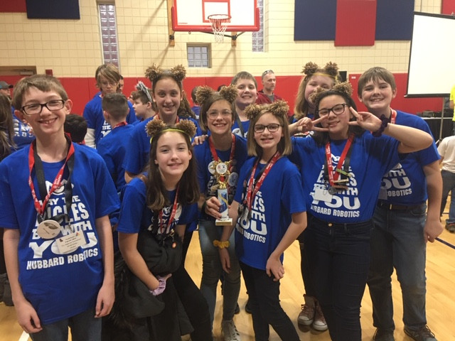 Robotics team at the robotics competition with trophy
