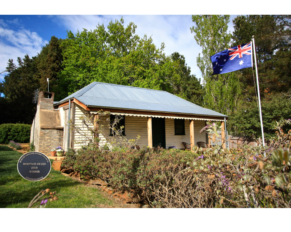Image of 150 year old Australian slab cottage with Australian flag flying