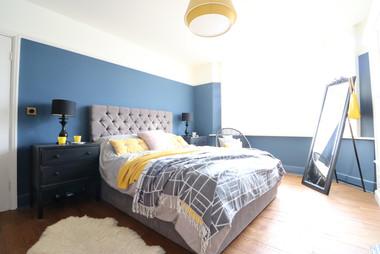 Master bedroom dark blue and mustard.JPG