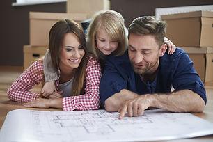 Eine Familie mit Mutter, Vater und Tochter schauen sich einen Grundriss einer Wohnung an. Im Hintergrund stehen Umzugskartons.