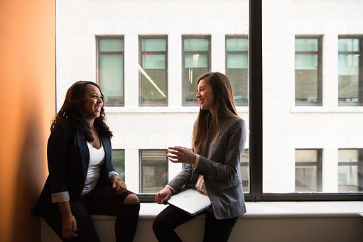 Two female coworkers conversing by a window