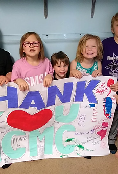 Children at daycare holding 'Thank You' banner for MCMC.webp