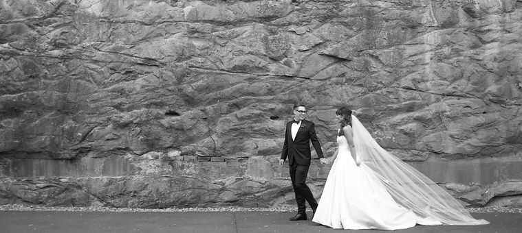 Groom holding brides hand walking down a sandstone wall