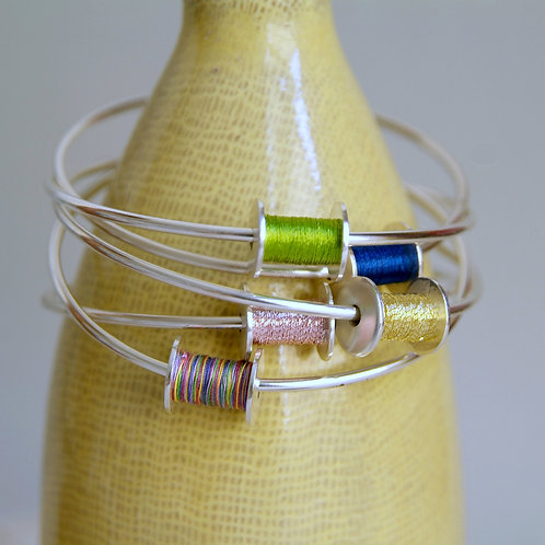 Stack of Ladies Silver Bangles with Silver Sewing Bobbins