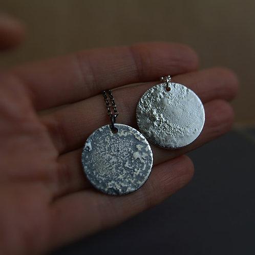 Full Moon Silver Pendants on a hand
