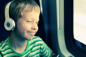 autistic child wearing headphones on tra