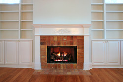 lit fireplace surrounded by built in bookshelves