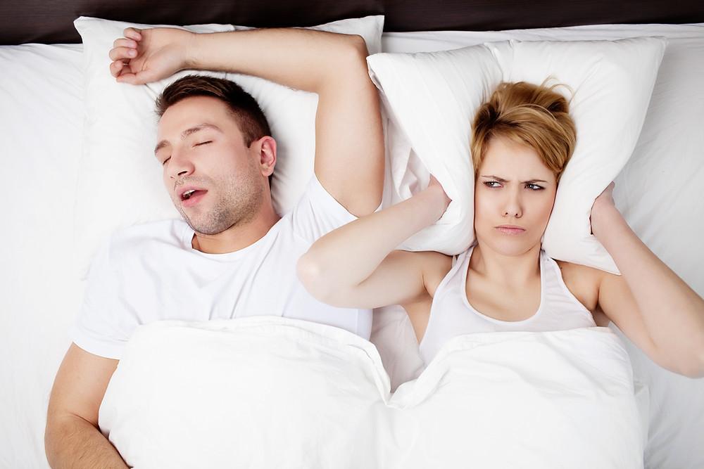 Sleeping man next to woman who can't sleep