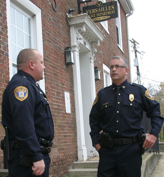 VERSAILLES POLICE CHIEF James Fugate, right, shown talking to Lt. Michael Fortney shortly after being appointed chief in November 2015, will retire at the end of August after 22 years of service.  (Photo by John McGary)