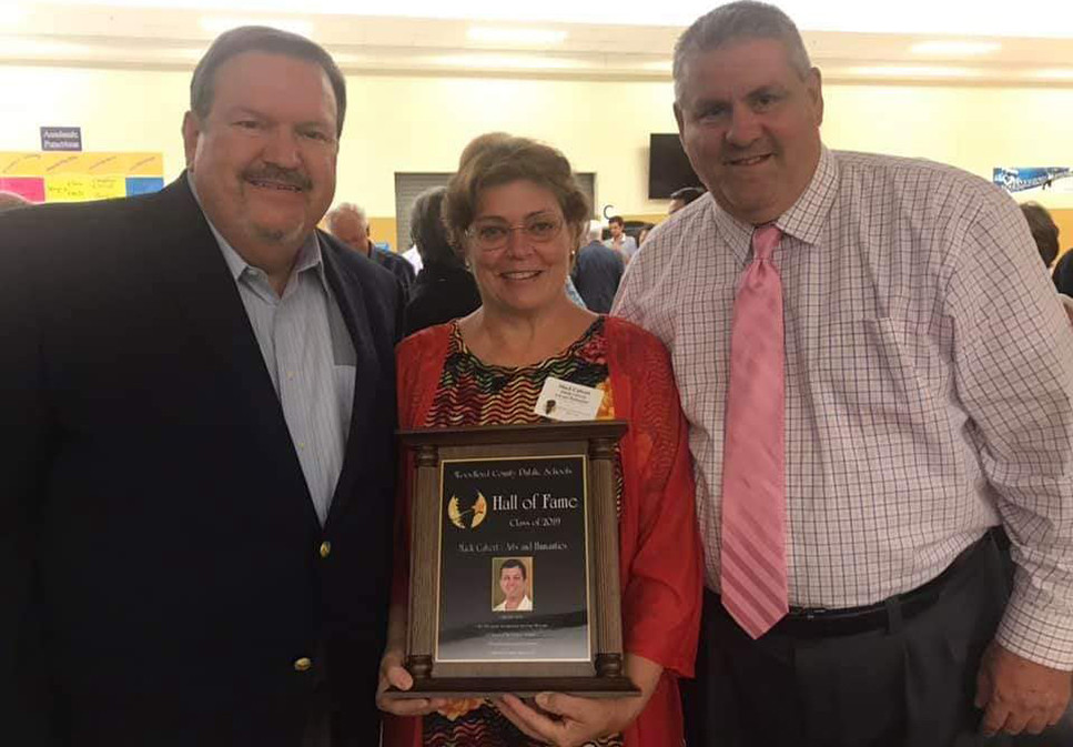 SHEILA CALVERT holds the Hall of Fame plaque for her late husband Mack, a member of the WCPS Hall of Fame Class of 2019. Flanking Sheila are Mack's former broadcast partners, Gary Ball, left, and Darrin Douglas. (Photo submitted)
