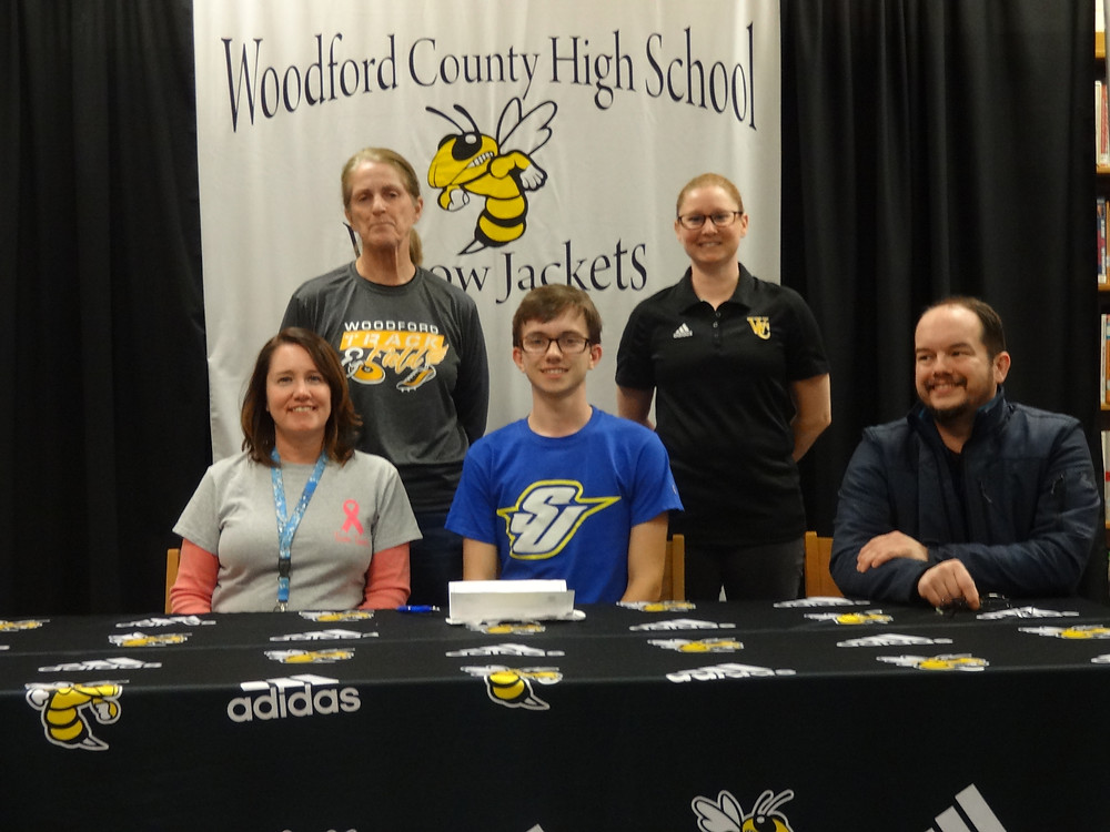 WCHS SENIOR PETER MCGOWAN signed his letter of intent to run track and field and cross country for Spalding University at a ceremony held on March 20.at the WCHS library. Pictured from left: Front row: Peter's mother Dana McGowan, Peter and his father Tim McGowan. Back row: WCHS track Coach Tracey Sobolewski and WCHS cross country coach  Brooke Stickel. (Photo submitted)