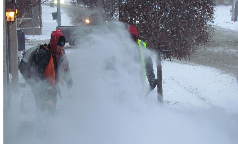 SOMETIMES SNOW REMOVAL crews get a little free assistance: An inmate from the Woodford County Detention Center helped blow snow off the sidewalk near the Versailles Municipal Building on Jan. 16. (Photo by John McGary)