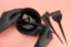 Girl in black gloves mixes hair dye in a