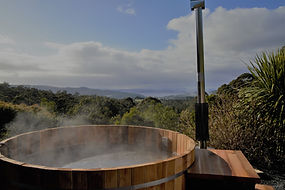 Steaming outdoor onsen hot tub with view of ocean and mountain