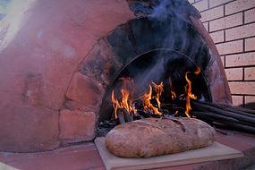 Outdoor wood fire piza oven baking gourmet bread