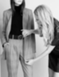 An image consulting expert styling a business outfit on a model