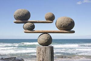 rocks-balancing-on-driftwood--sea-in-bac