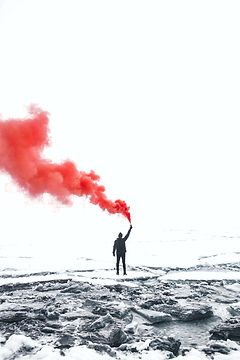 A person holding a flare with red smoke: better find, see and use info on violent extremism.