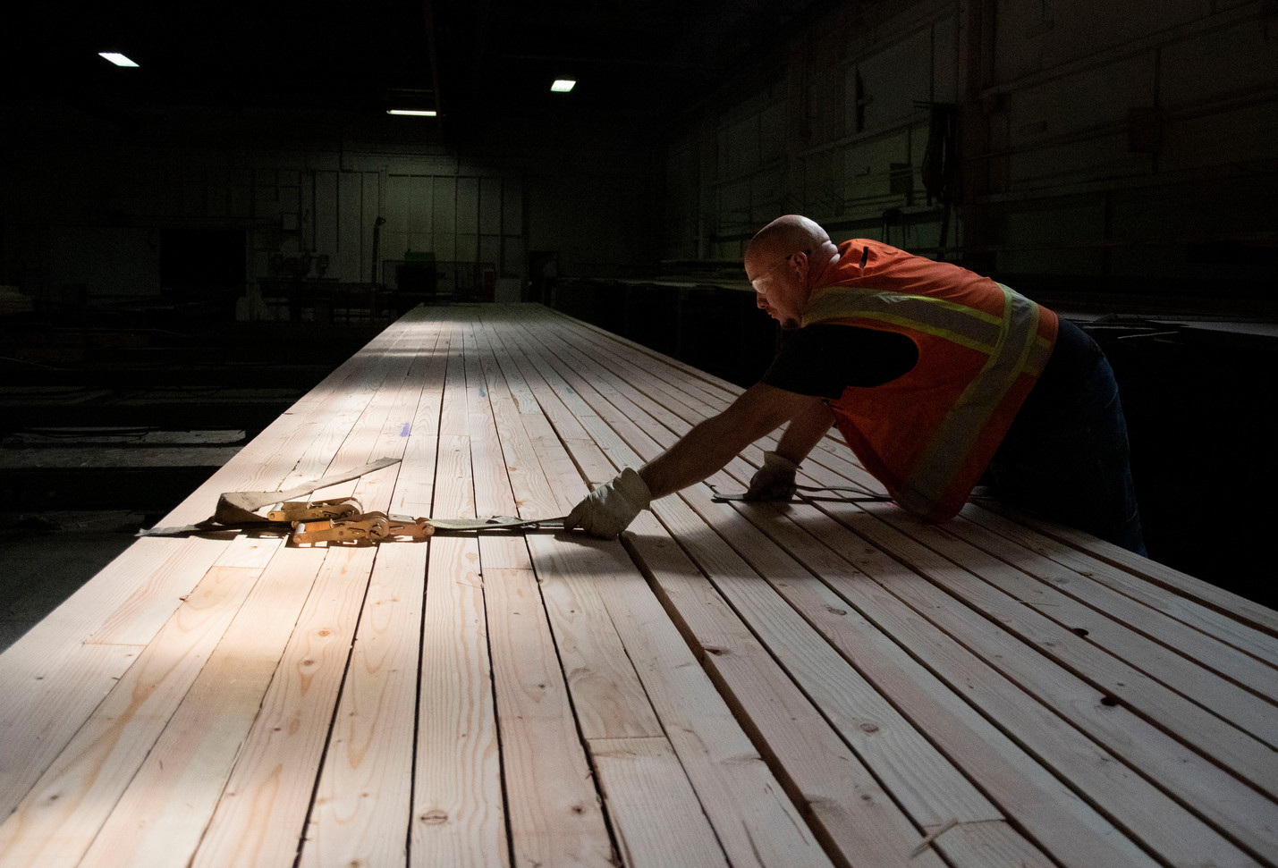 A mill worker at Rosboro Lumber Company straps newly milled lumber together. 2019