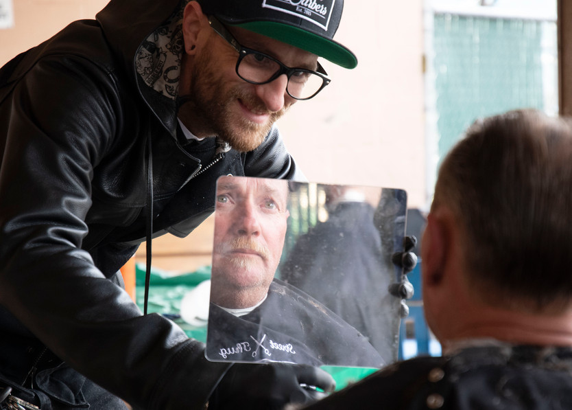 Kellen of Street Thug Barbers shows a guest of the Eugene Mission the final product after a free haircut for Veteran's Day, 2018. Street Thug Barbers brings together barbers who volunteer their time to serve those experiencing houselessness.