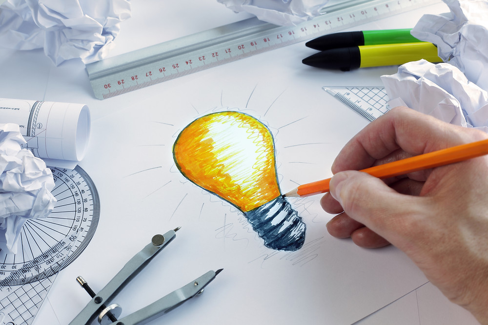 Designer drawing a light bulb, concept for brainstorming and inspiration.jpg