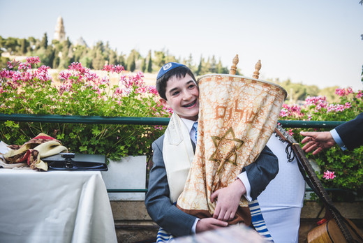 Bar Mitzvah Boy at Mt. Zion Hotel in Jerusalem holds Torah.