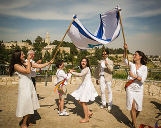 Bat Mitzvah girl dances with family in a chuppah at Yemin Moshe.