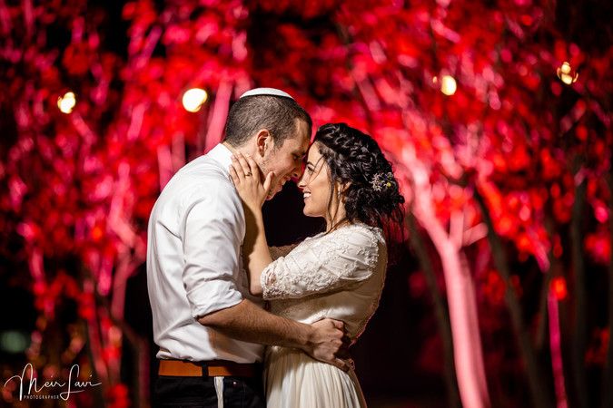 Bride and groom embrace in the Jerusalem night sky.