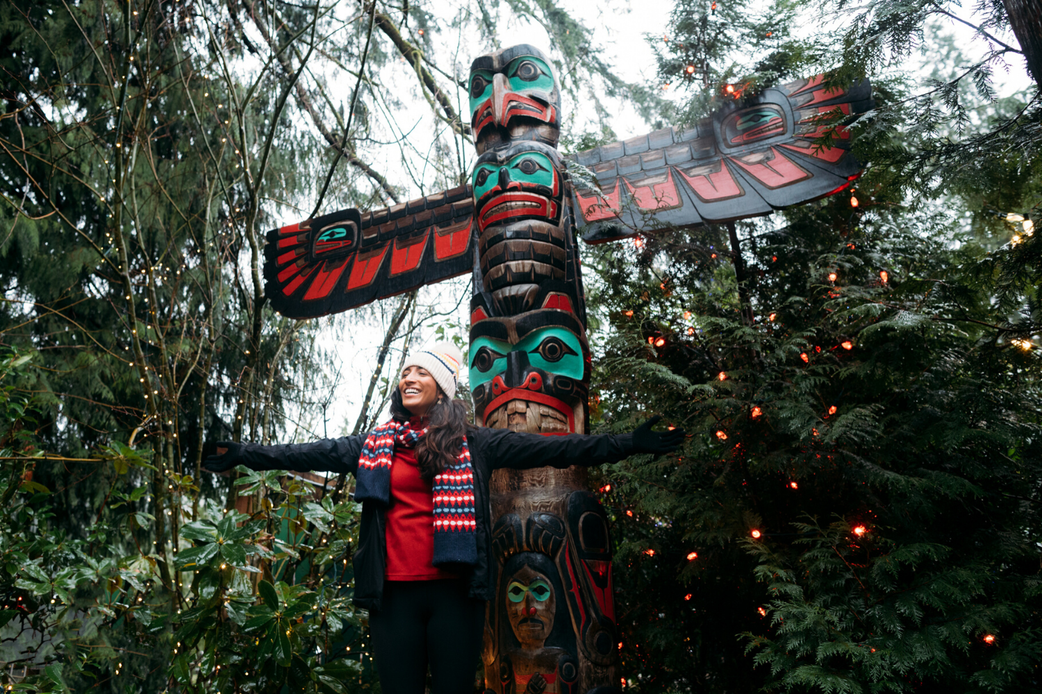 Woman posing with story pole at Capilano Suspension Bridge Park