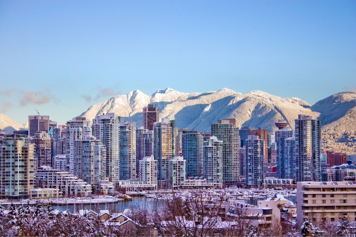 Snowy rooftops and False Creek looking north towards Vancouver's downtown skyline with snow filled mountains.