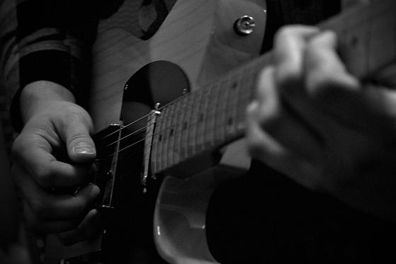 Guitar teacher strumming an electric guitar
