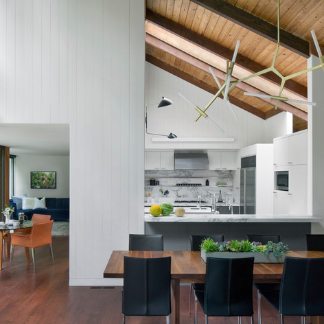 Sonoma Retreat: The team decided to keep the original midcentury modern wood ceilings in the living room and chose to reconfigure the U-shaped layout of the kitchen by removing a wall separating the space from the dining room and living room and creating two runs of counters centered around a marble-wrapped island. Photo credit: David Wakely Photography