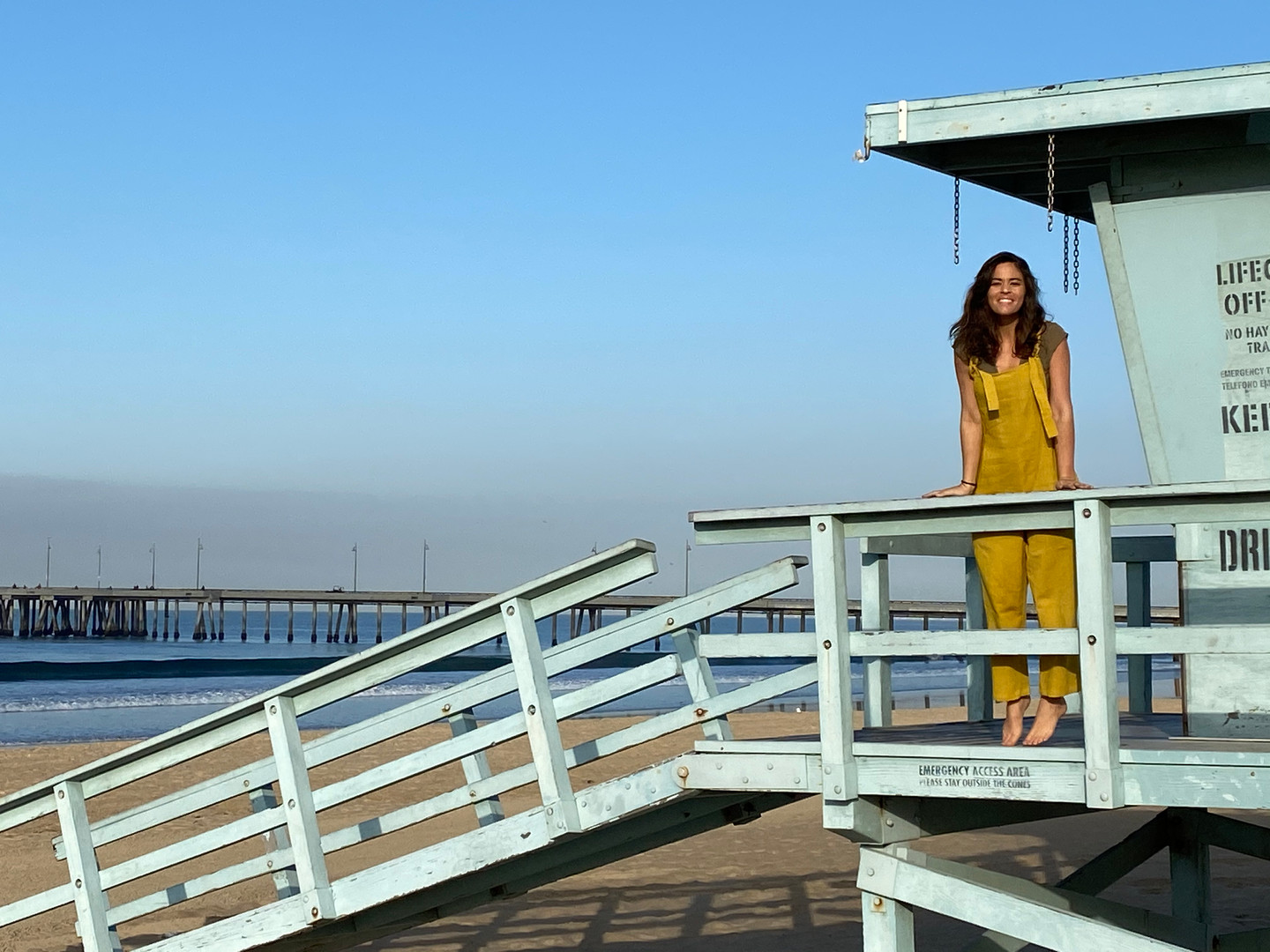 hanging out in yellow jumsuit on a life guard stand at the beach